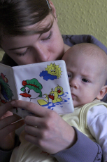 Adult reading book to baby