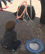 Young boy makes bubbles with bubble wand at Maryland Day
