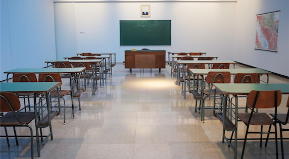 Empty classroom with a blank chalkboard and chairs and desks