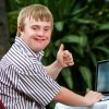 Young man with disability gives thumbs up while working on computer