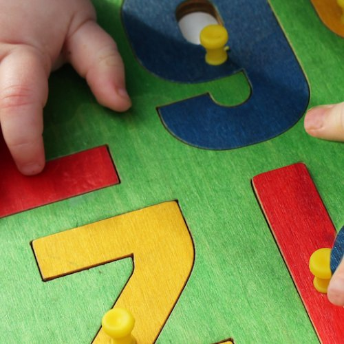 Baby places numbers in puzzle