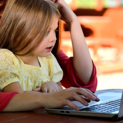 Image of child and parent on laptop