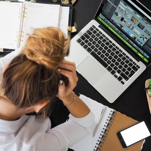Stressed person surrounded by work and laptop