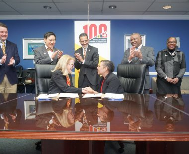 Dean Rice and PGCPS CEO Monica Goldstone shake hands at MOU signing