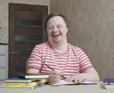 A student with a disability sits at a desk with a pen and notebook